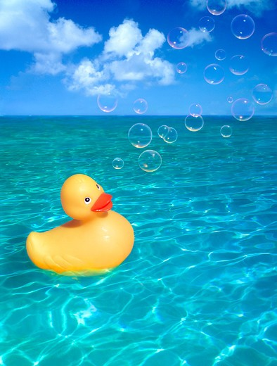 Stock Photo: 4286-53150 Cheerful yellow rubber duckie floating on calm water outdoors under blue sky with clouds and bubbles.