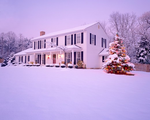 Stock Photo: 4286-53162 Snowy winter view of exterior of two story white frame house with front porch and tree lit with Christmas lights.  Property released.