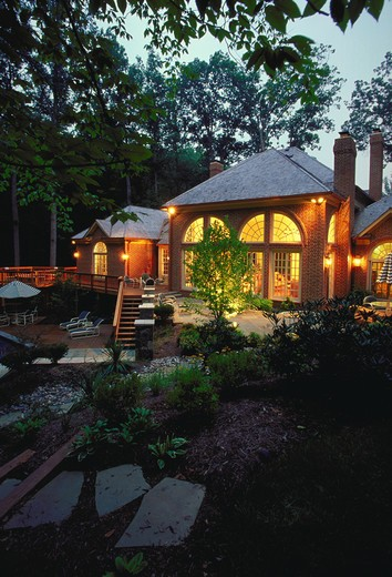 Stock Photo: 4286-53486 Exterior view of a brick colonial with elaborate pool and patio at dusk.  Property released.