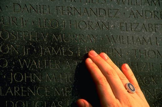 Wende Ruffin, daughter of James Ruffin who was killed in action during the Vietnam war, touches her father's name at the Vietnam Memorial, Washington, DC. (model released) : Stock Photo