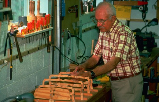 Retiree works on a model boat in woodworking shop at retirement center in Maryland. (model released) : Stock Photo