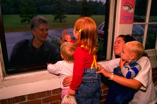 Children say good-bye to parents through a window at a private day care center in Providence, Rhode Island. : Stock Photo