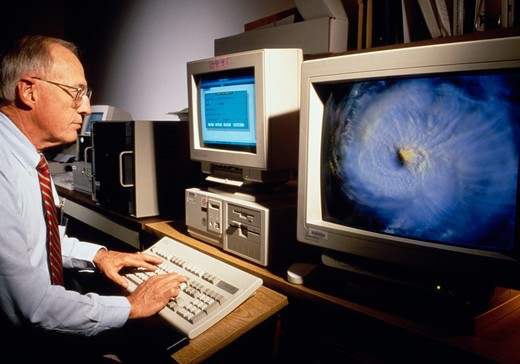 William M. Callicott, computer specialist at the National Oceanic & Atmospheric Administration (NOAA), with an image of Hurricane Emily on screen. Washington, DC. (model released) : Stock Photo