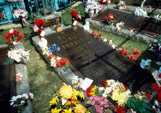 Stock Photo: 4286-54878 Flowers and small offerings bedeck the grave of musician Elvis Presley in the Meditation Garden at Graceland, Memphis, Tennessee.