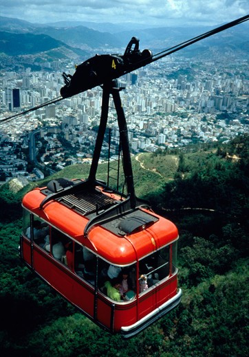 Stock Photo: 4286-54895 The teleferico cable car ascends Mount Avila National Park with downtown Caracas, Venezuela in the background.