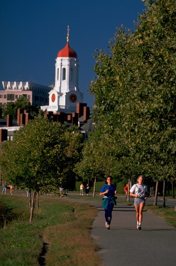 Stock Photo: 4286-54914 Two women jog along path on banks of Charles River with Harvard University's Dunster House at rear, Cambridge, Massachusetts.