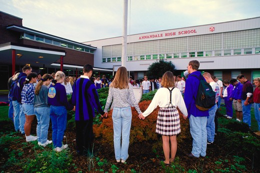 Annandale High School students join hands, circle the flag pole, and pray in front of their school during National Student Prayer Day in Annandale, Virginia. : Stock Photo