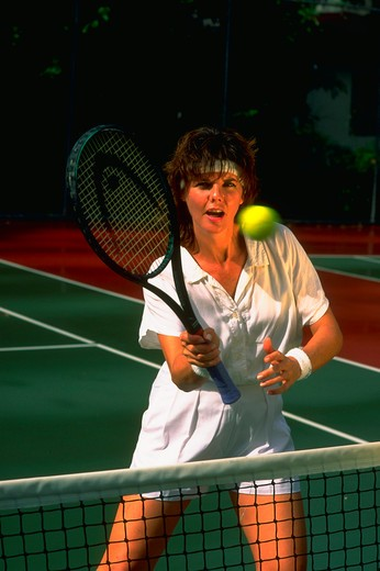 Woman hitting tennis ball at the net. : Stock Photo