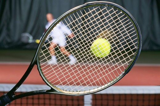 Stock Photo: 4286-56198 Tennis game, seen throught the racket of one player.