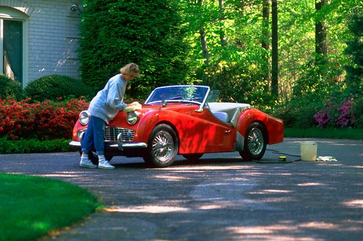 Stock Photo: 4286-56482 A young girl washing and waxing a vintage  TR3 convertible in the driveway outside her house.