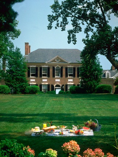 Stock Photo: 4286-56490 Portrait of the main hose at Woodlawn Plantation in Virginia with a large green lawn. In the foreground on the law a picnic blanket and lunch are set out. Property Release available.