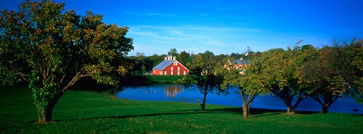 Stock Photo: 4286-56510 The pond at the Carroll County Farm Museum in Maryland surrounded by trees with a red barn in the background.
