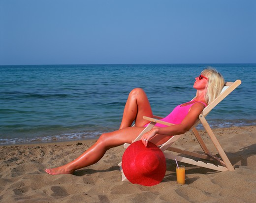 Stock Photo: 4286-56591 Blonde woman in pink bathing suit sitting on a deckchair on the beach and holding a large red sun hat.