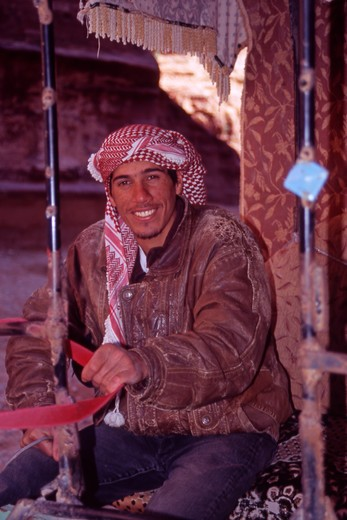Stock Photo: 4286-56751 Portrait of a young, smiling Jordanian man who takes Tourists through the Siq on his two - wheeled buggy. Petra, Jordan.