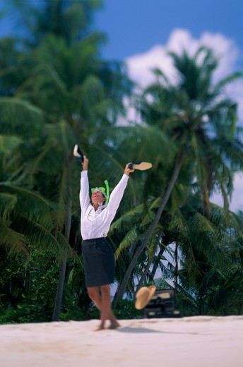 Businesswoman in skirt, white blouse and green snorkel tosses her shoes overhead on a sunny, sandy beach of the Maldives Islands. : Stock Photo