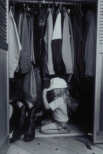 Black and white image of a young girl kneeling on her father?s closet floor trying on her dad?s hat. : Stock Photo