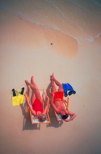 Stock Photo: 4286-57637 Aerial view of a couple wearing bathing suits sitting in chairs on the beach at the edge of the water with their snorkel masks and fins along side them.