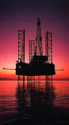 An off shore oil rig in the Gulf of Mexico silhouetted against a purple sunset. : Stock Photo