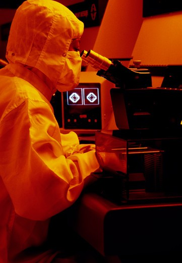 Stock Photo: 4286-57737 A lab technician wearing protective gear examining an item under a microscope in the lab.