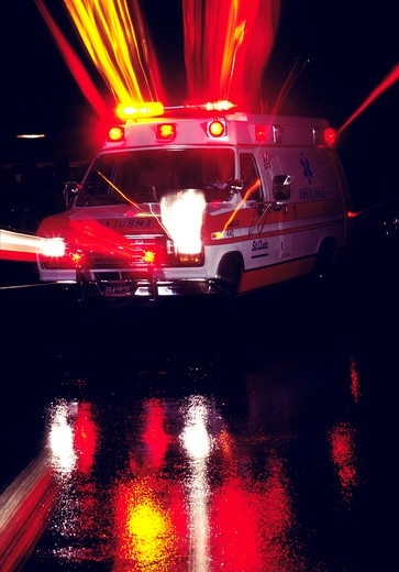 Stock Photo: 4286-57756 An evening image of an ambulance its lights that are reflecting onto the road.