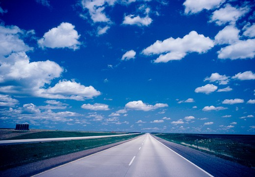 A partly, cloudy sunny day  image of a straight road into the distance, Kansas, U.S.A.. : Stock Photo
