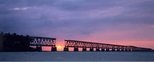 Sun sinks toward Atlantic Ocean, framed by historic and abandonded rail road bridge at Bahia Honda State Park, the Florida Keys, Florida. : Stock Photo