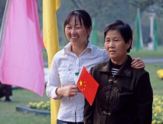 Grown daughter and mother pose for photograph in park during National Day holiday, Beijing, China : Stock Photo