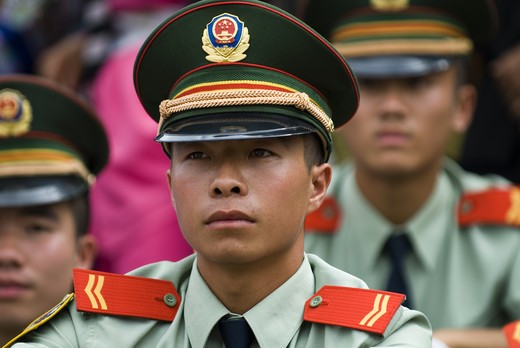 Stock Photo: 4286-58276 Local police officers watch festivities during annual June Torch Festival at Long Lake Town, Shilin County, Yunnan Province, China.