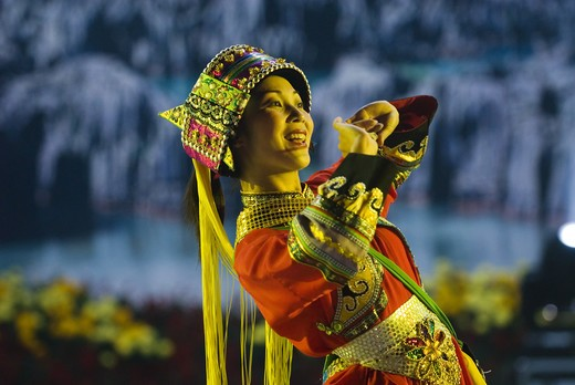 Performer wears costume of the Sani ethnic minority at stadium performance culminating annual Torch Festival, Shilin, Yunnan Province, China. : Stock Photo