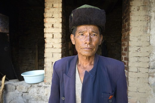 Elderly member of Yani ethnic minority group proudly poses with Communist Party member red lapel pin outside his modest home, Qingkou Village, Yuanyan County, Yunnan Province, China. : Stock Photo