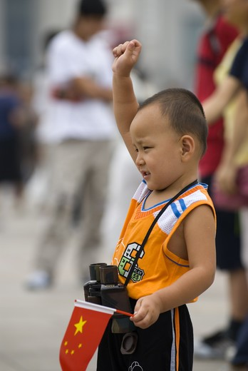Stock Photo: 4286-58325 Wearing western sport clothes and posing for parent's snap shot, young boy salutes and hold's Chinese flag during outing at Tiananmen Square, Beijing, China.