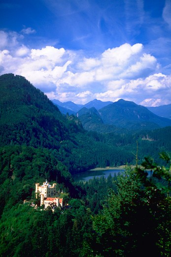 View of King Ludwig?s Homenschwangau Castle, Bavaria, Germany  with lush green mountains, countryside, and blue sky with clouds in the background. : Stock Photo