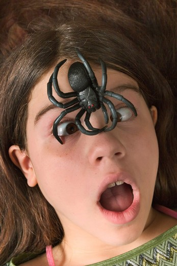 Stock Photo: 4286-58647 Girl posing with a fake rubber spider sitting on her forehead.  MODEL RELEASED.