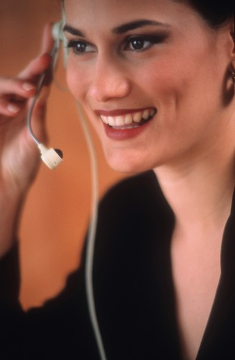 Latino business woman with telephone headset. : Stock Photo