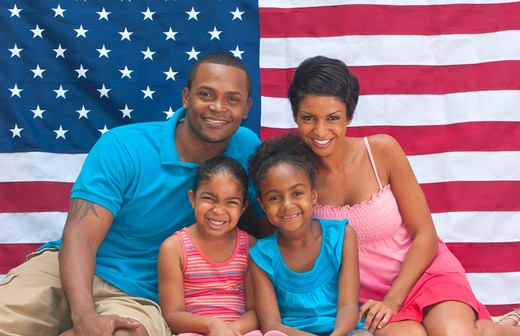 Black African American family loving the USA with flag and colors of holiday celebration : Stock Photo