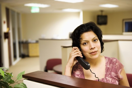 Portrait of a businesswoman talking on the telephone in an office : Stock Photo