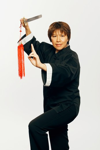 Stock Photo: 4286-59601 Portrait of a mature woman practicing martial arts with a sword