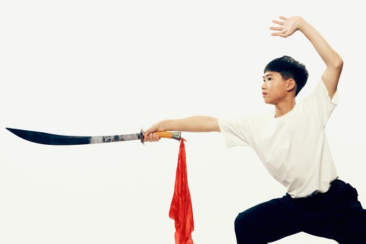 Stock Photo: 4286-59604 Boy practicing martial arts with a sword