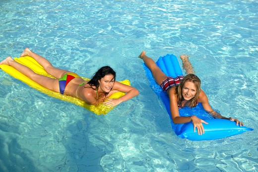 Stock Photo: 4286-61495 two women having fun with air mattress in the pool