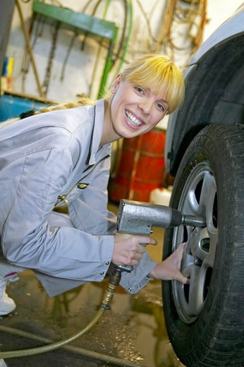 Stock Photo: 4286-61646 female motor mechanic changing car wheel