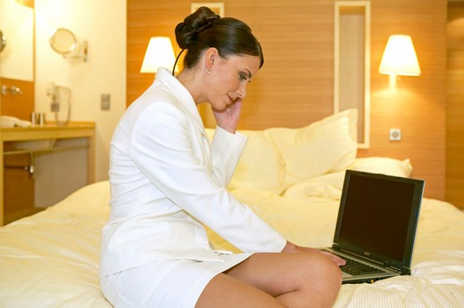 young woman in suit working on notebook in hotel room : Stock Photo