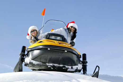 two women on snowmobile, skiscooter : Stock Photo