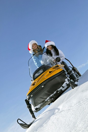 Stock Photo: 4286-62439 two women on snowmobile, skiscooter