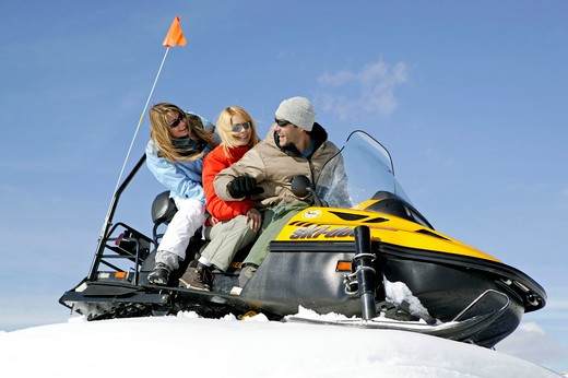Stock Photo: 4286-62441 Two Women and Man on Ski Scooter Winter Holiday