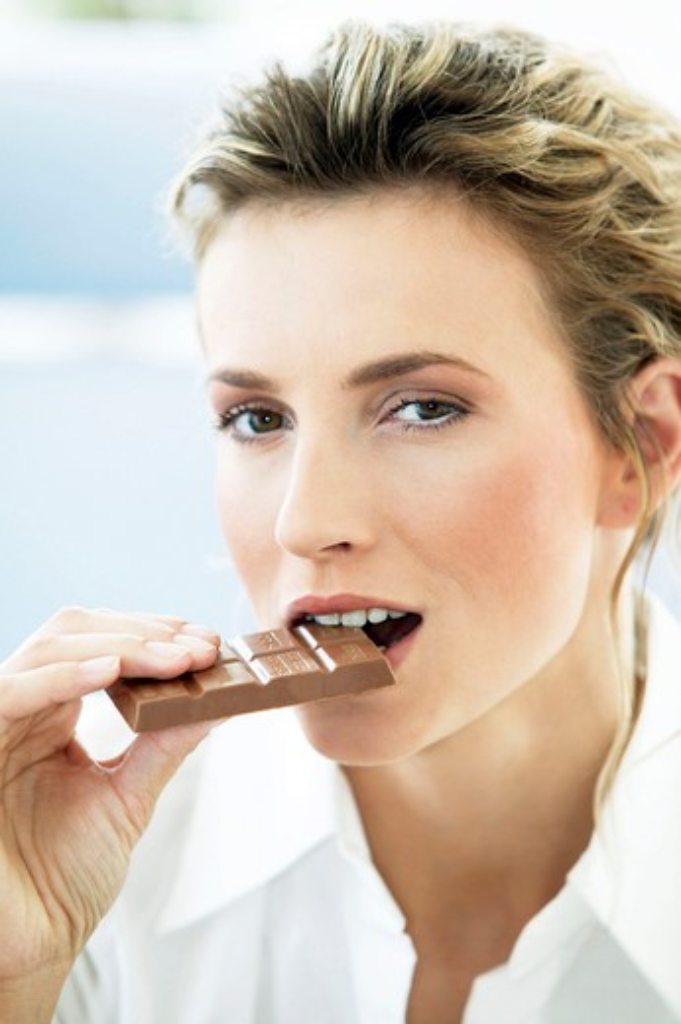 young woman eating big bar of chocolate : Stock Photo