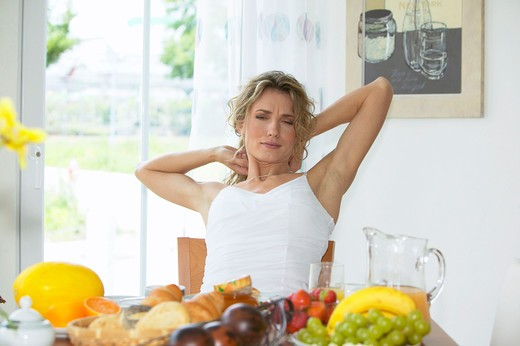 woman having breakfast streching herself : Stock Photo