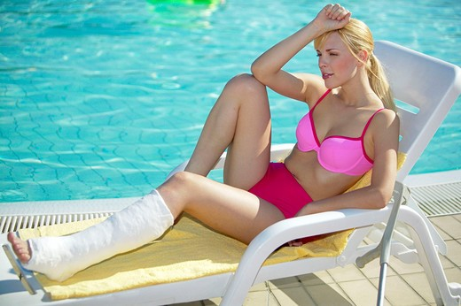 woman with leg in cast at the pool : Stock Photo