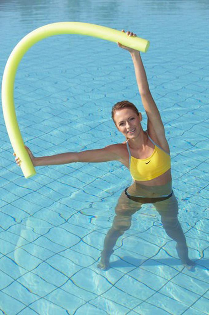 Stock Photo: 4286-63358 young woman doing aquaaerobic in the swimmingpool