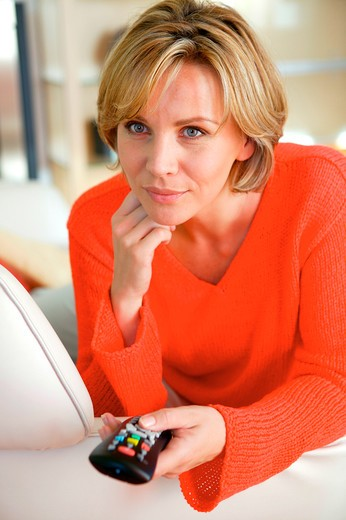 blond woman at home with remote control : Stock Photo