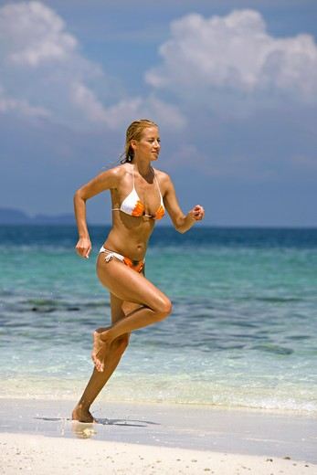 sexy blond woman jogging on tropical beach in  Krabi : Stock Photo